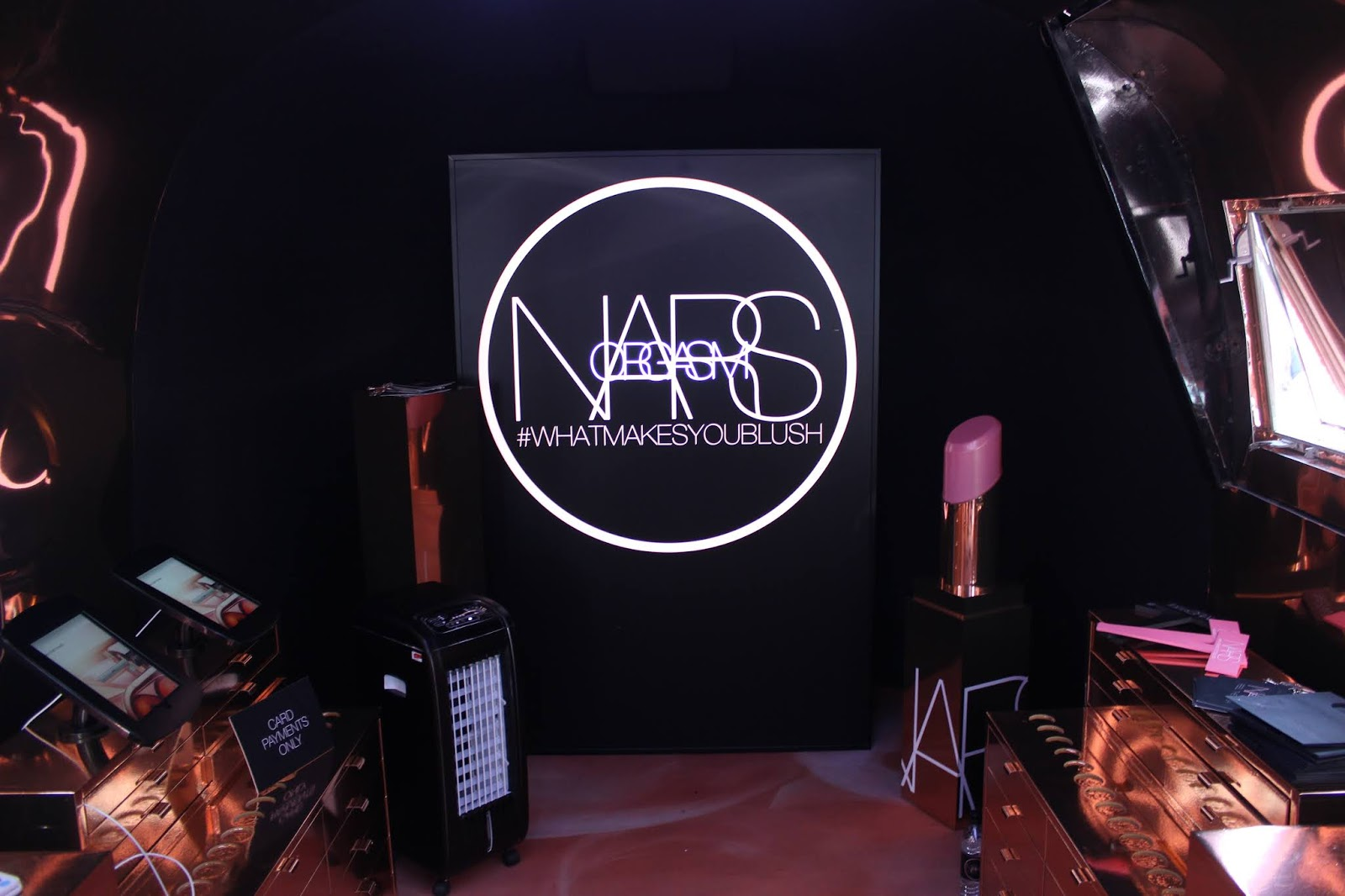 A Nars Orgasm Tour Bus sign with large lipstick