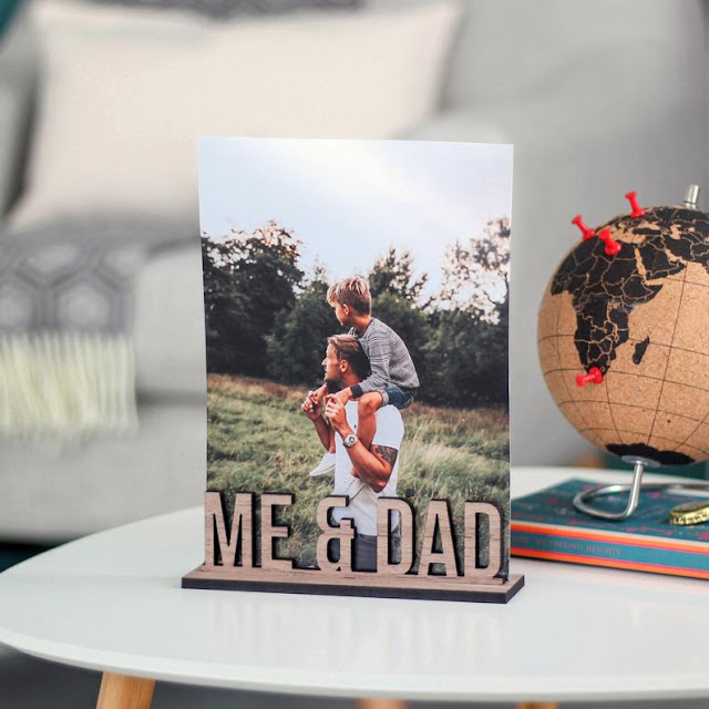 a wooden photo holder with the words 'ME & DAD' lasercut out of the wood. It is holding a photo of a boy on his father's shoulders.