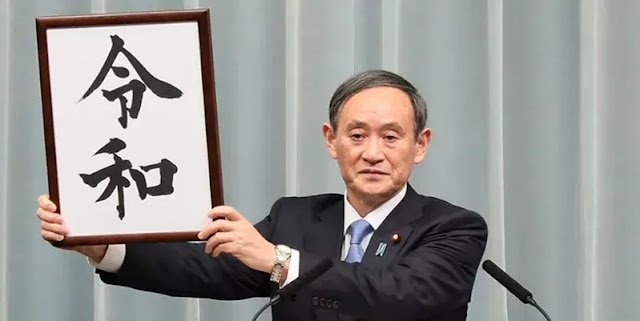 "Image Attribute: Japan's Chief Cabinet Secretary Yoshihide Suga announces the new Imperial era ""Reiwa"" to the press. / Date: April 1, 2019 / Source: Wikipedia"