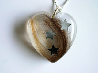 Keepsake pendant containing two locks of hair and stars