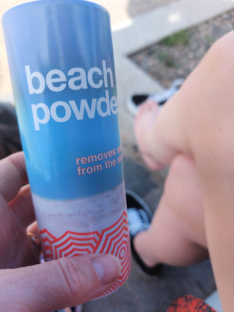 A blue tube of Beach Powder held close up to the camera, with a foot in the background