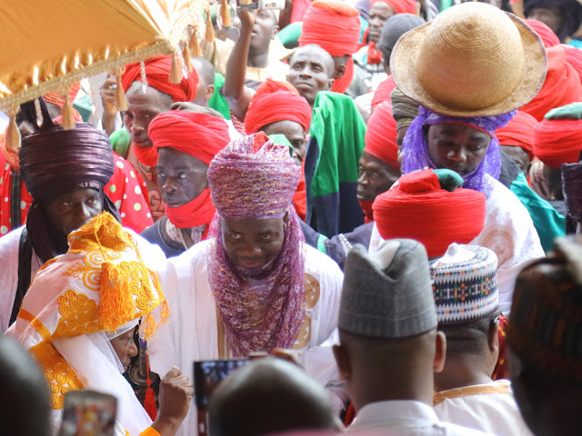 under his orange-embroidered hood, the Emir of Zazzau, Shehu Idriss, arrives at the Palace