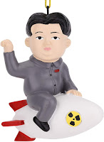 A man with dark hair and grey clothing sitting on s white rocket - meant to be Kim Jon Un, the leader of North Korea.