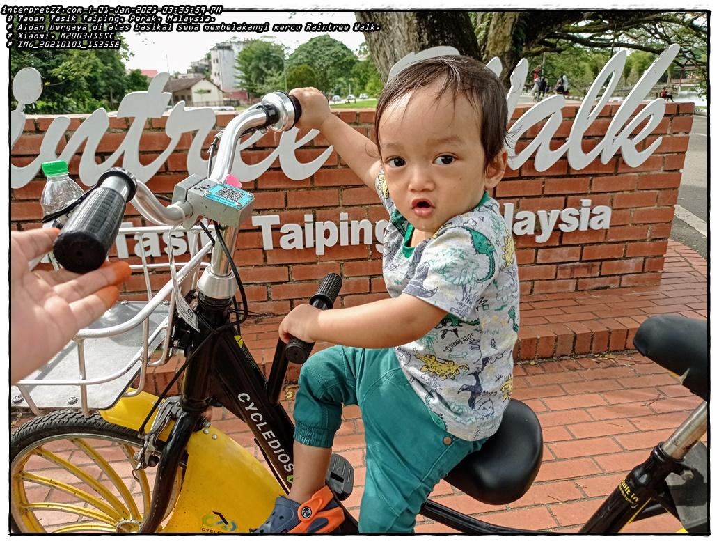 Aidan bergaya di atas basikal sewa di Raintree Walk di Taman Tasik Taiping, Perak, Malaysia.