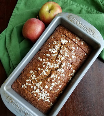 sliced loaf of applesauce oatmeal quick bread back in loaf pan with apples
