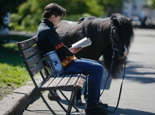 A young man is resting in a city square in the center of Ukrainian Slaviansk next to his pony. Photo taken on April 27, 2014 in a still peaceful city.