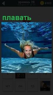 В бассейне под водой плавает девушка в купальнике, волосы в разные стороны, помогая себе руками