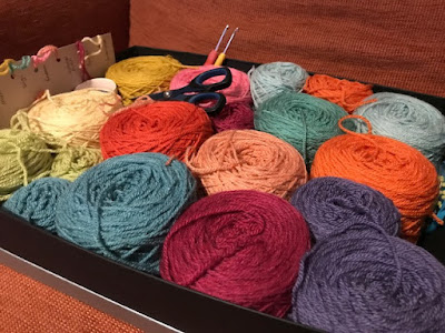 Balls of yarn in a box ready for a crochet blanket project
