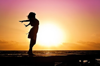 Girl on pier with arms outstretched at sunset