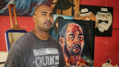 Myuran Sukumaran stands in front of a self-portrait in Kerobokan's workshop.