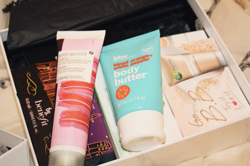 korres hand lotion and bliss body butter tubes sitting in a glossy box
