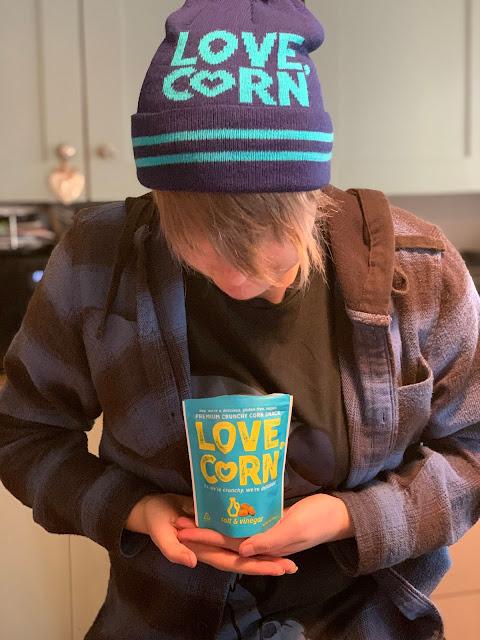 teen wearing LOVE CORN hat holding Love Corn packet
