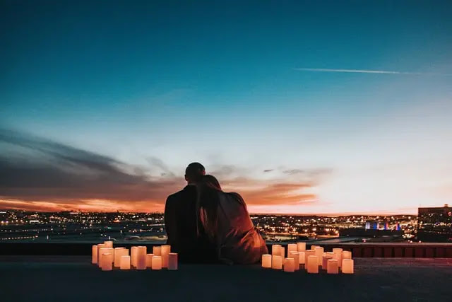 Pareja sentada de espaldas entre muchas velas encendidas mirando a la ciudad