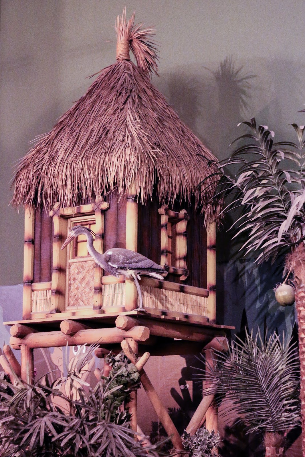 a photo of a tiki hut in paradise island adventure golf that has a fake pelican perched on it.