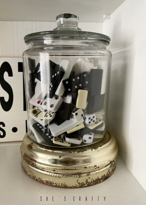 Jar of vintage game pieces as a collection displayed on a cupboard.