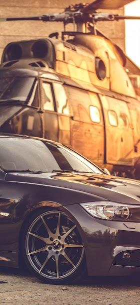 خلفية سيارة BMW سوداء اللون تقف بجانب مروحية