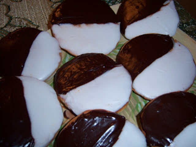 These are called half moon cookies. The cookies are frosted half white and half chocolate frosting. . These are famous in Utica New York bakeries and a local cookie there.  These cookies are also referred and named black and whites in some states.