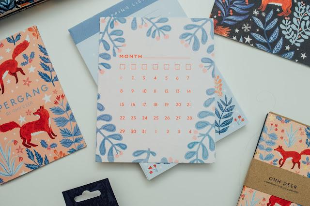 A blank calendar card with a leafy print around the edge