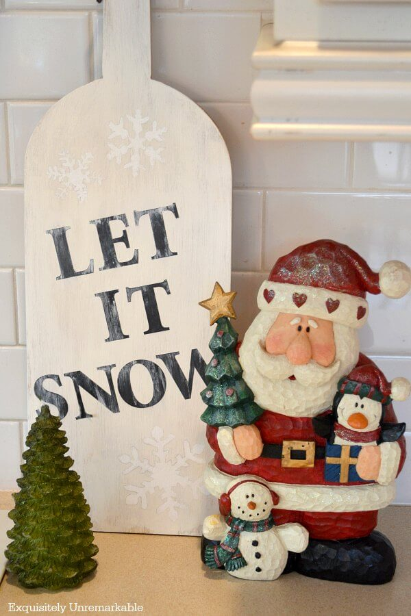 Let It Snow Wooden Sign sitting on countertop near Santa figurine and tree candle