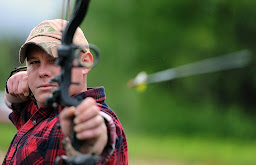 An archer who is really focused and still having just shot an arrow