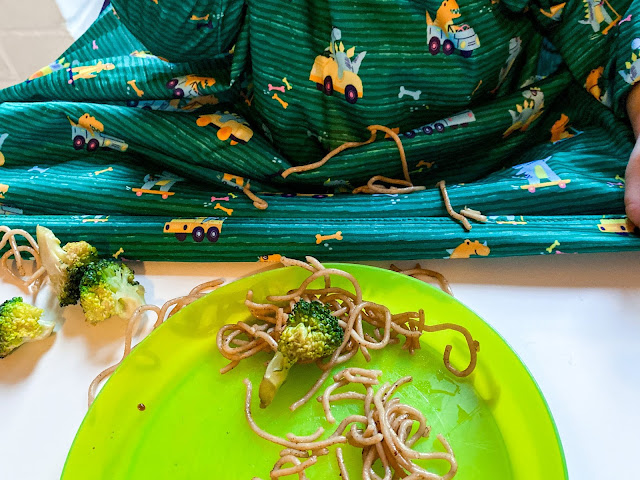 Close up of a plate, noodles and broccoli spilt around the plate and on the catchall bib