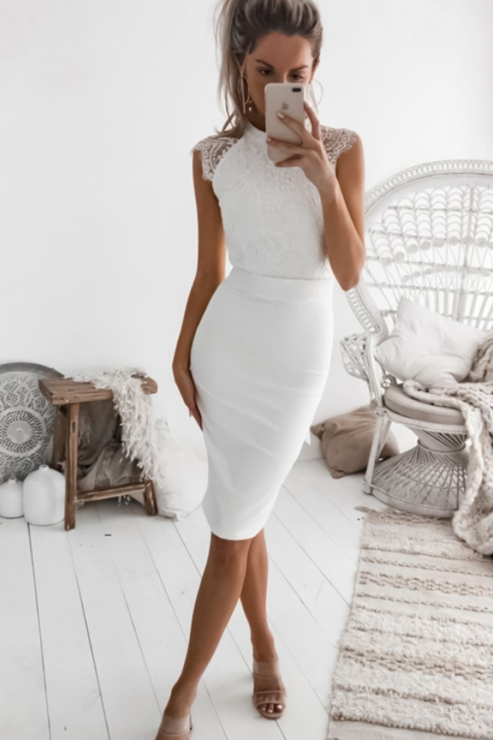 woman in a tight dress is posing in a room and taking selfie