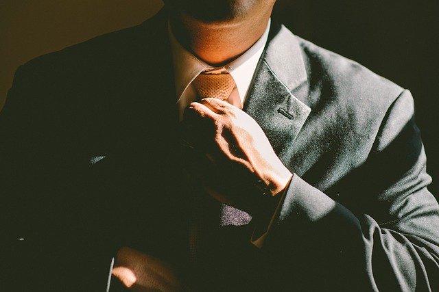 pria gagah yang sedang memegang dasinya
