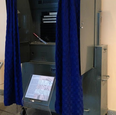 Gear and lever style voting machine with gray metal structure and blue privacy curtain