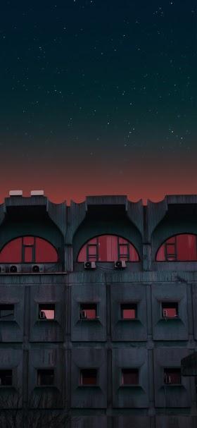 خلفية مباني صناعية داكنة تحت نجوم السماء ليلاً
