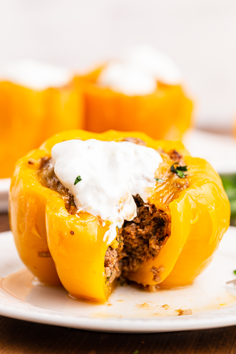 Photo of a Keto Slow Cooker Mexican Stuffed Pepper on a white plate with a bite cut out of it.