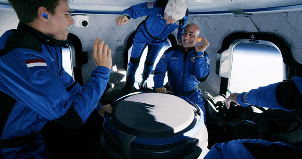 Oliver Daemen, Wally Funk, Mark Bezos and his brother, Amazon.com founder Jeff Bezos (not fully visible) float inside the New Shepard capsule 105 kilometers (65 miles) above the Earth...on July 20, 2021.