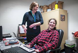 """Abby Duffy ir Konkordo mokyklos tiflopedagogė Adrienne Shoemaker smagiai ruošiasi kitai pamokai. Nuotraukoje mokinė sėdi prie kompiuterio, prie kurio prijungta Brailio eilutė """"Braille Edge""""."""