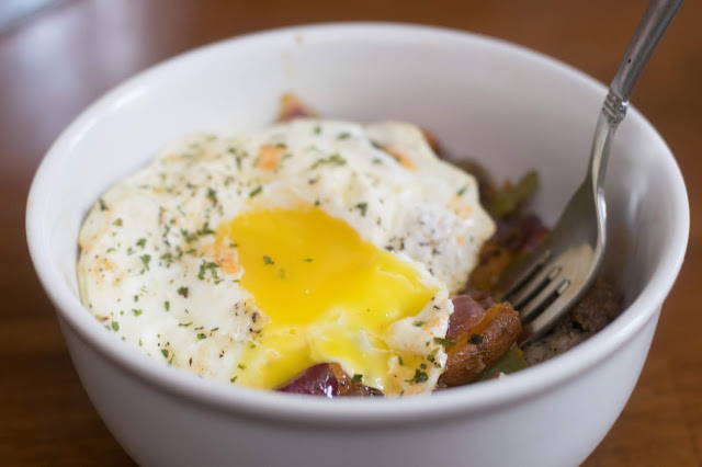 The sweet potato hash in a bowl, with the egg on top, and the yolk oozing out.