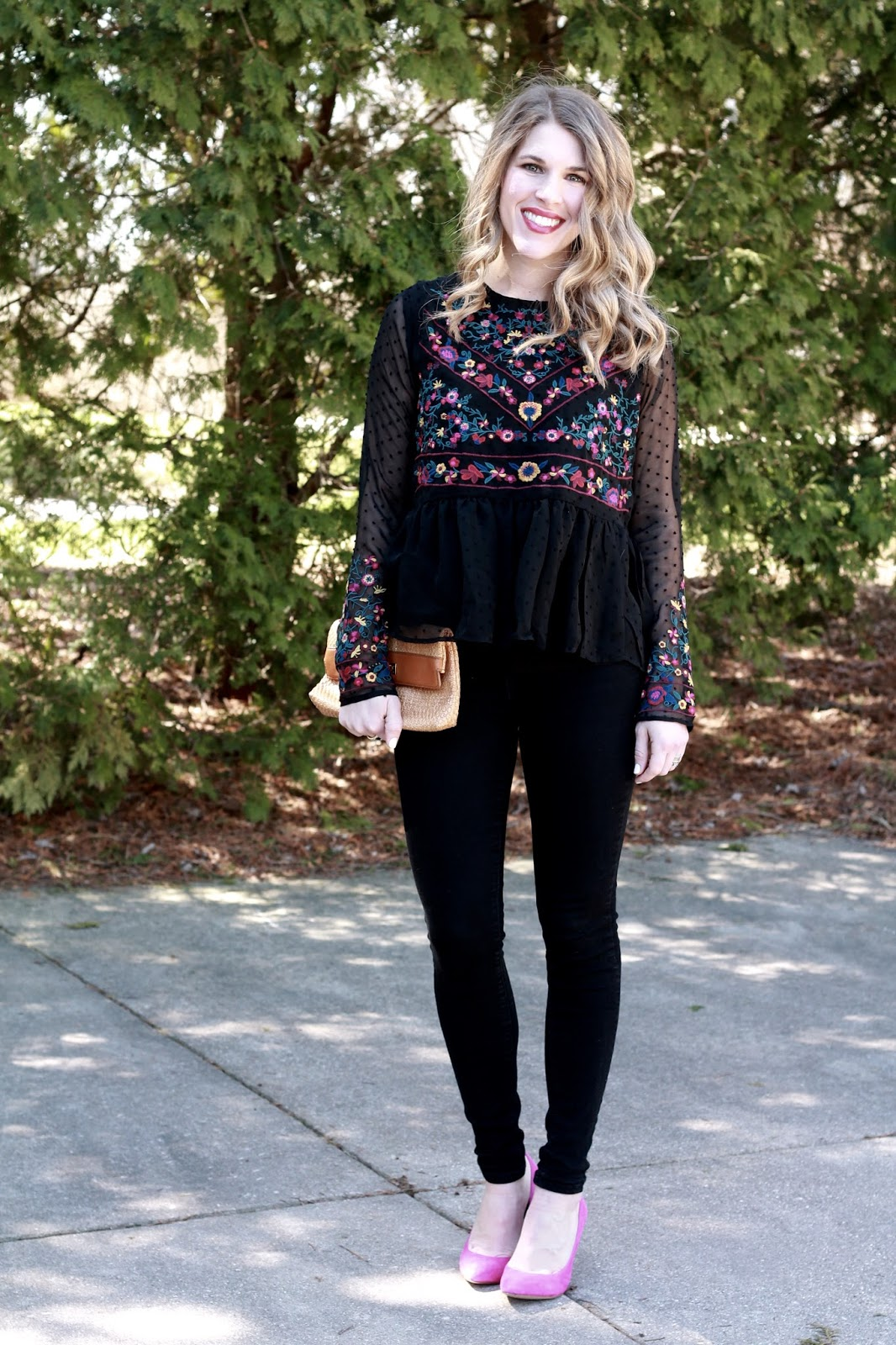 sheer black embroidered peplum blouse, black jeans, pink heels, straw clutch,
