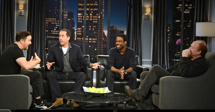 Ricky Gervais, Jerry Seinfeld, Chris Rock, and Louis C.K. in plush chairs talking and gesturing