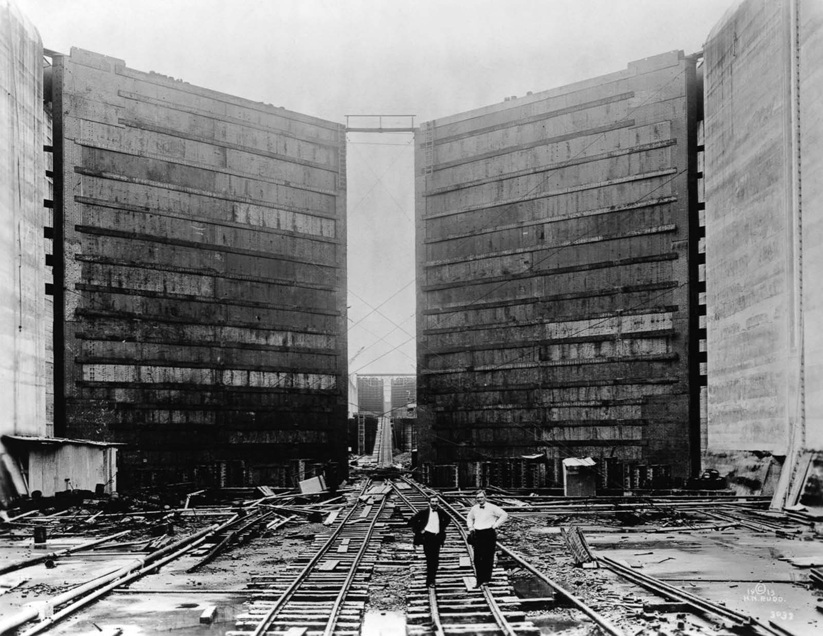 Engineers stand in front of the massive gates of the canal locks. 1913.
