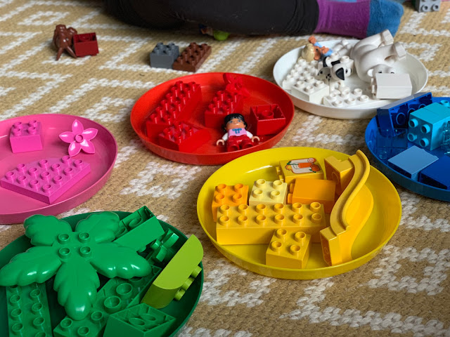 Coloured plates with coloured LEGO DUPLO pieces as sorted by a toddler for a development play idea