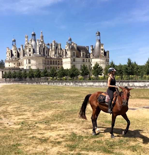 Horseback rider posing in front of the Chambord castle in Loire valley