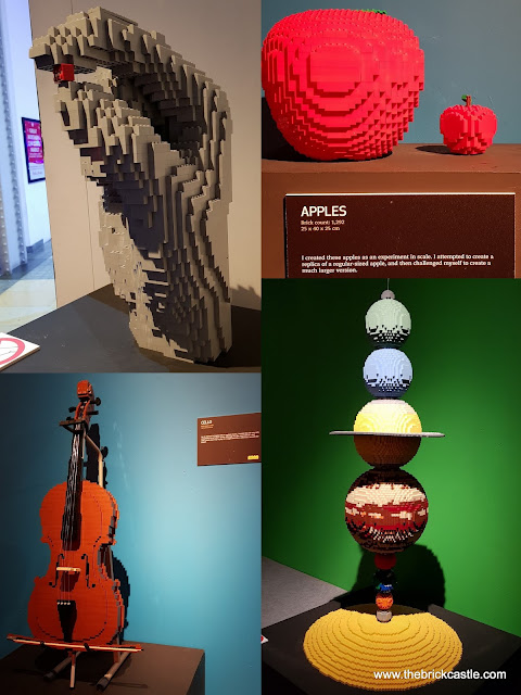 The Art Of THe Brick Apples Planets solar system cello and hand gripping LEGO brick