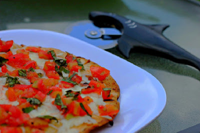 grilled pizza with tomatoes and fresh basil on a white plate with pizza cutter in the background