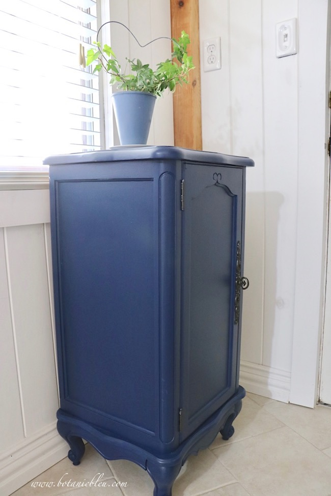 Add French Country style to a room with a small Provence style cabinet painted navy to go with wall cabinets