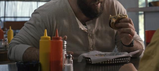 Vemos un primer plano de los botes de ketchup (rojo) y mostaza (amarillo) una cesta con papel encima las patatas, y en la mano de un señor (Benny) media hamburguesa