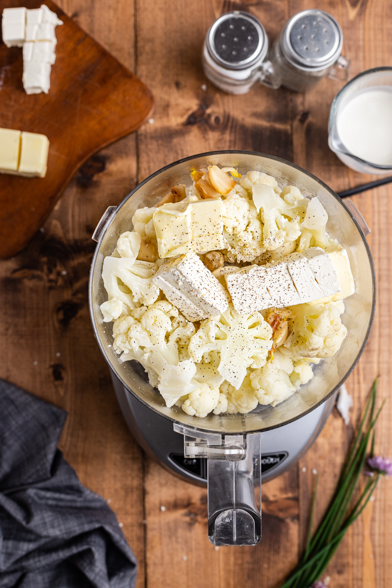 Ingredients for Roasted Garlic Mashed Cauliflower in a food processor.