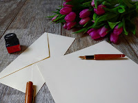 Picture of pen, paper, envelopes and ink bottle, for letter writing