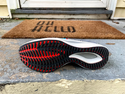 Ribbed pattern outsole seen. Heel has an exposed cutout to see fiber glass plate. Slight fork pattern seen in outsole. Exposed forefoot seen in red.