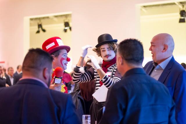 Artistas Palhaço e Mágico de Humor e Circo interagindo com convidados durante coquetel de relacionamento do evento de premiação da Abigraf em São Paulo.