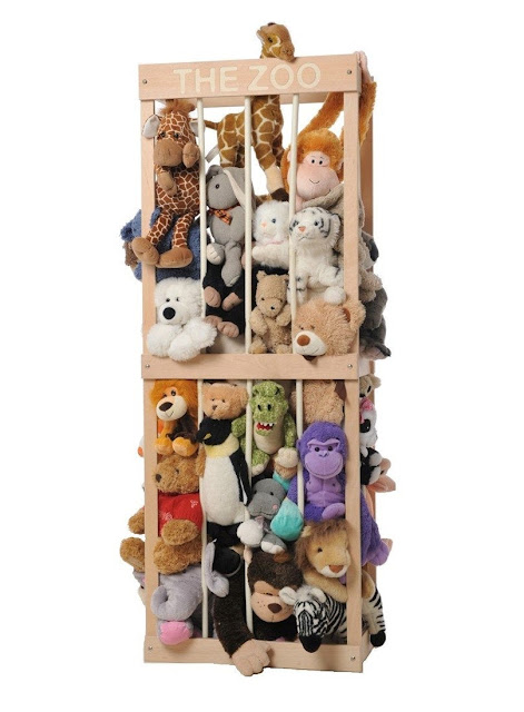 A crate style box made to look like a cage filled full of soft toys