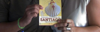 duas mãos segurando o guia do Caminho Português de Santiago