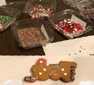 Gingerbread cookie in the shape of a train locomotive is decorated with colored sprinkles. Dishes of different types of sprinkles are in the background.