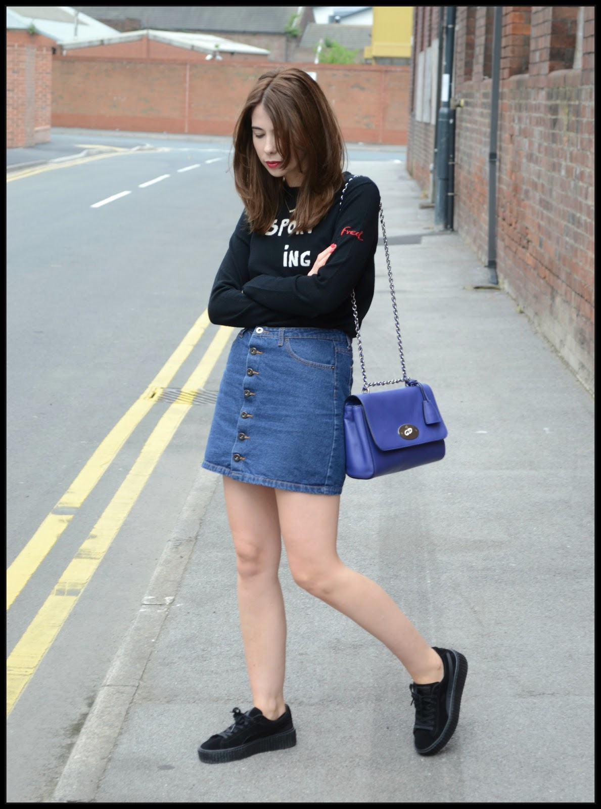 Bella Freud sporting Cashmere jumper, Denim button down skirt, Black creeper puma fenty trainers, Blue medium Lily Mulberry bag